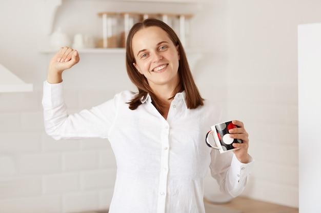Ritratto di donna felice in piedi con il braccio alzato, tenendo una tazza di tè, allungando le mani dopo il risveglio, guardando la telecamera con un sorriso affascinante, indossando una camicia bianca in stile casual.