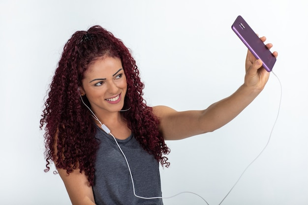 Portrait of a happy woman using cellphone and headphones, smiling and making a selfie. isolated on a white background.