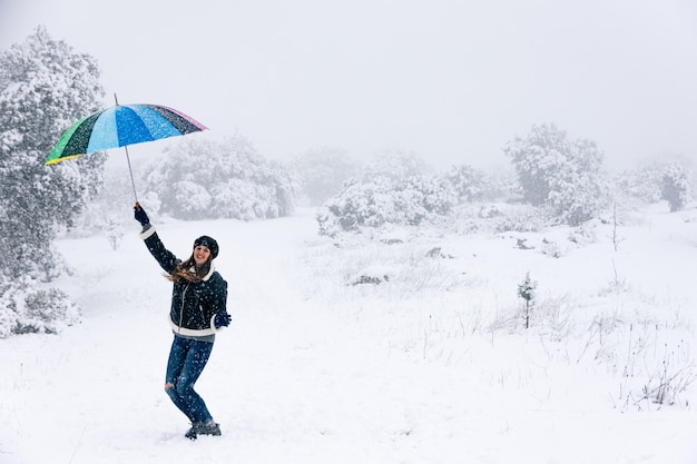 Portrait of a happy woman walking and holding a colorful umbrella during a snowfall.
