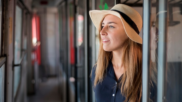 Portrait of happy woman wearing hat in train