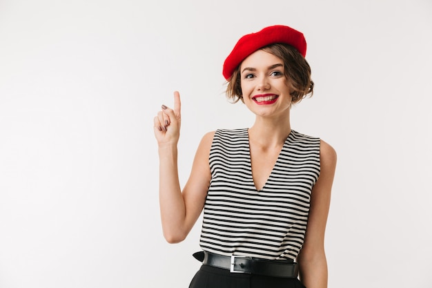 Portrait of a happy woman wearing red beret pointing