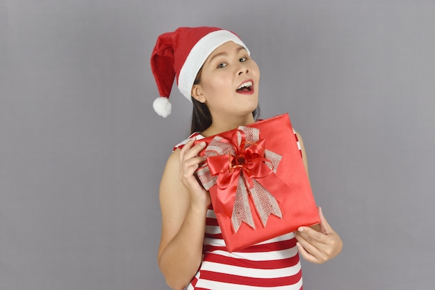 Portrait of happy woman wearing santa claus hat and holding gift box.