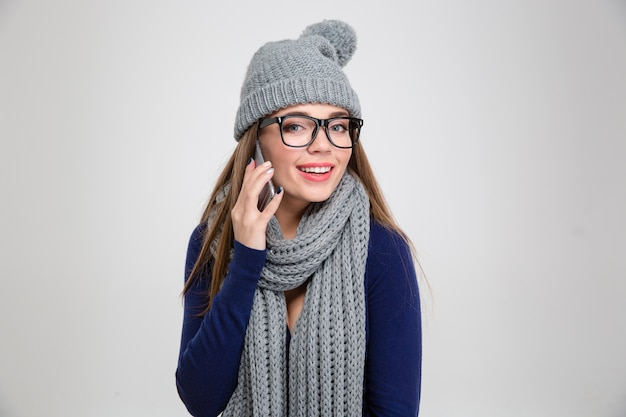Portrait of a happy woman in winter cloth talking on the phone and  isolated on a white wall