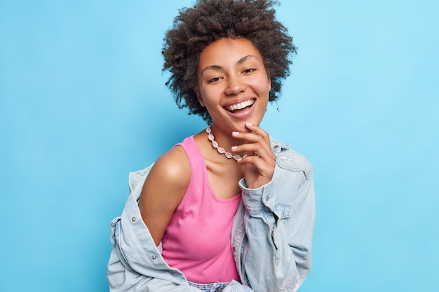Portrait of happy woman with afro hair toothy smile shows bare shoulder wears fashionable clothes isolated over blue wall