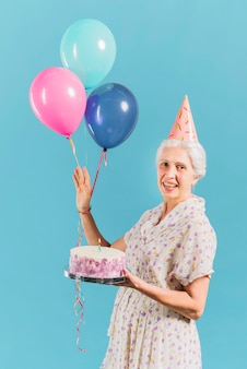 Portrait of a happy woman with birthday cake and balloons on blue backdrop