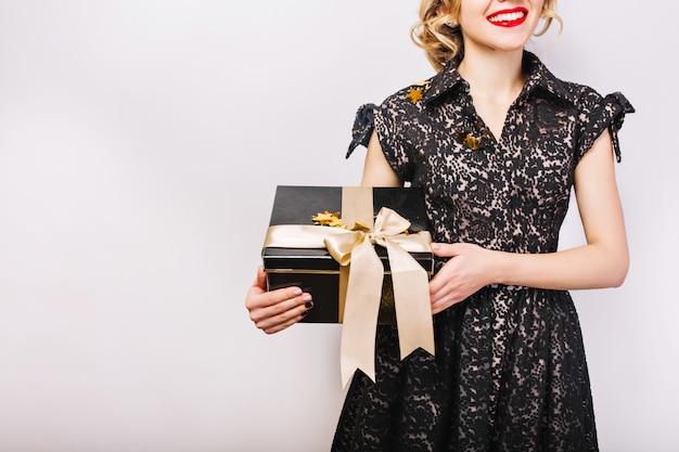 Ritratto di donna felice con confezione regalo nera in mano, labbra rosse, vestito nero, sorriso.
