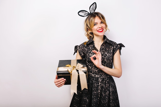 Portrait happy woman with black gift box in hand, red lips, black dress, smile.