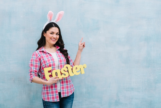 Portrait of a happy woman with bunny ears on head holding easter word pointing finger upward on blue background