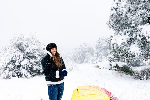 Portrait of a happy woman with a colorful umbrella during a snowfall.