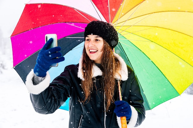 Portrait of a happy woman with a colorful umbrella making a photo during a snowfall.