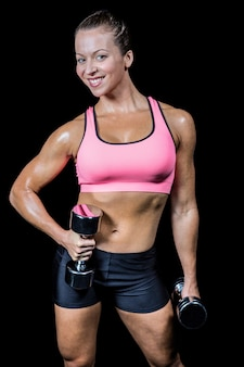 Portrait of happy woman with dumbbells
