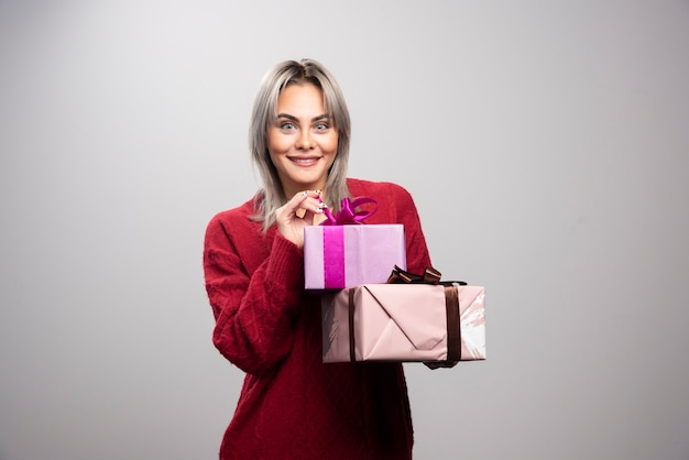 Portrait of happy woman with gift boxes posing. Free Photo
