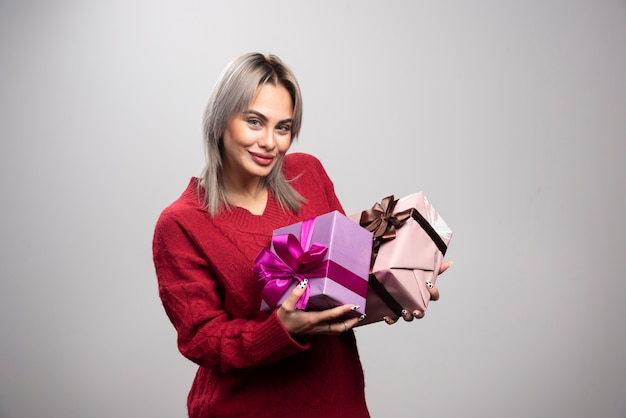 Portrait of happy woman with gift boxes posing.