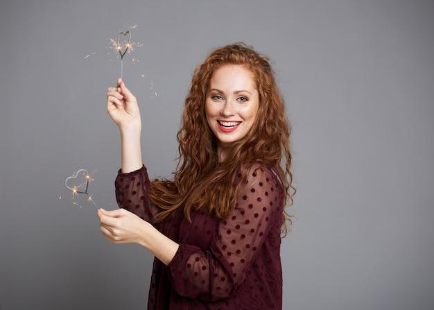 Ritratto di donna felice con stelle filanti a forma di cuore