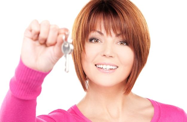 Portrait of happy woman with keys over white wall