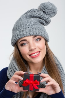 Portrait of a happy woman with scarf and hat holding jewelry gift box isolated on a white background