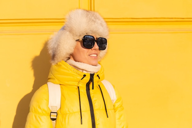 Portrait of a happy woman with a smile in snow-white zabas in winter against a yellow wall on a sunny day in a warm russian siberian hat