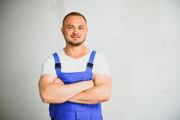 Изолированный работник портрета счастливый, в униформе, на белой предпосылке. концепция ремонтных услуг