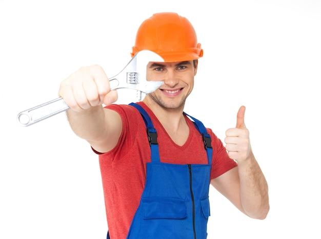 Ritratto del lavoratore felice con la chiave che mostra i pollici aumenta il segno isolato su bianco