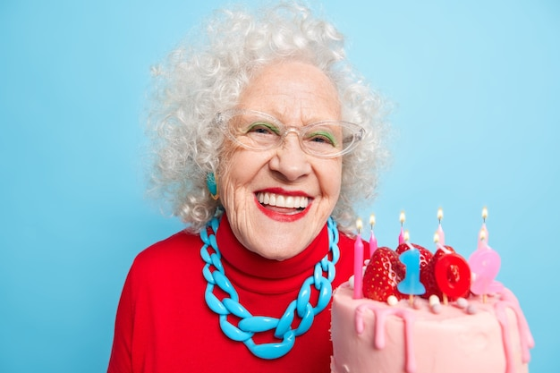 Portrait of happy wrinkled elderly woman smiles pleasantly has festive mood celebrates 102nd birthday wears transparent glasses red jumper necklace going to make wish while buring candles on cake