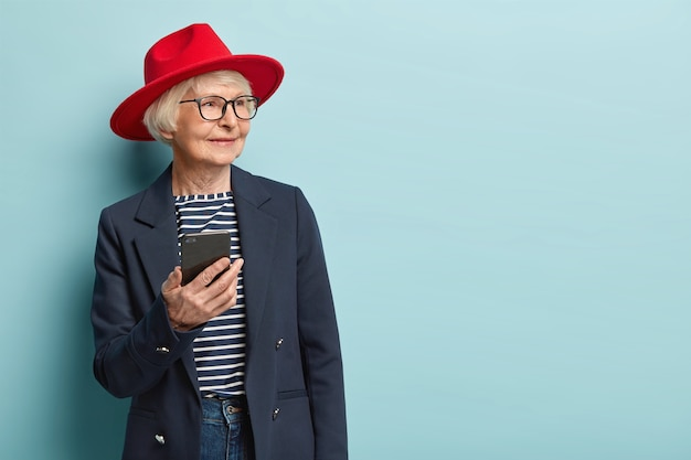 Portrait of happy wrinkled woman looks aside, waits for call, holds modern cellular, learns how use modern technology, wears red headgear, coat, models over blue wall, free space for information