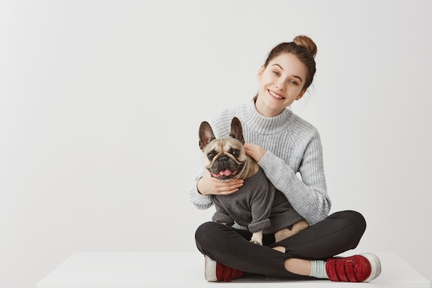 Portrait of happy young adult in good mood sitting on table at home crossed legs. happy housewife fondling french bulldog with pleasure. copy space, family concept