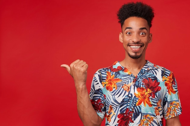 Portrait of happy young african american guy, wears in hawaiian shirt, looks at the camera with cheerful expression, stands over red background and broadly smiles, points to the left at copyspace.