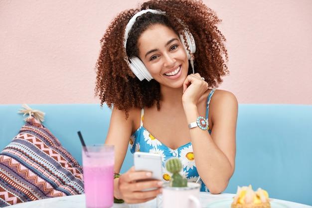 Ritratto di giovane donna afroamericana felice con capelli scuri croccanti, ascolta la trasmissione radiofonica, collegata allo smart phone moderno e alle cuffie bianche