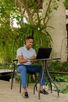 Portrait of happy young african businessman wearing casual clothes and sitting at coffee shop while using laptop computer and social distancing