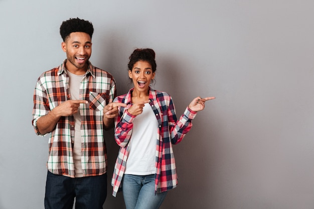 Portrait of a happy young african couple standing together pointing side with fingers Free Photo
