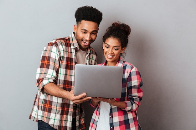 Portrait of a happy young african couple using laptop computer