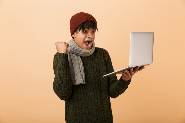 Portrait of a happy young african man dressed in autumn clothes isolated over beige wall, holding laptop computer, celebrating