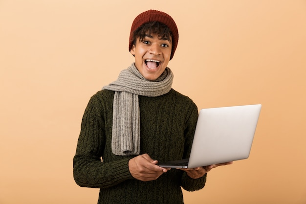 Portrait of a happy young african man dressed in autumn clothes isolated over beige wall, holding laptop computer