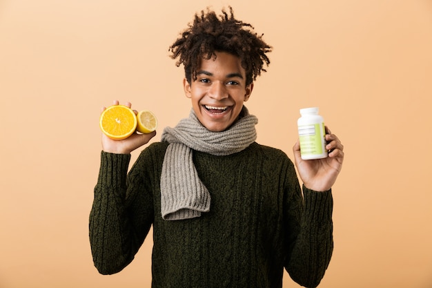 Portrait of a happy young african man dressed in autumn clothes isolated over beige wall, showing container with pills and half of an orange
