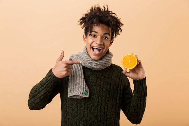 Portrait of a happy young african man dressed in autumn clothes isolated over beige wall, showing pills capsules and half of an orange, pointing