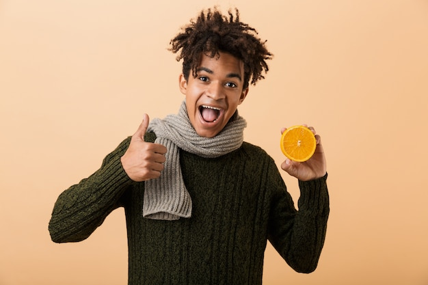 Portrait of a happy young african man dressed in autumn clothes isolated over beige wall, showing pills capsules and half of an orange, thumbs up