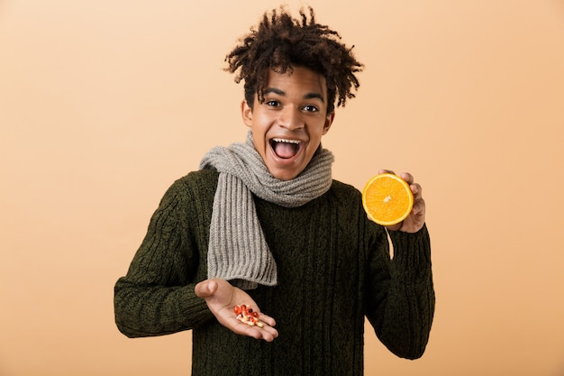 Portrait of a happy young african man dressed in autumn clothes isolated over beige wall, showing pills capsules and half of an orange