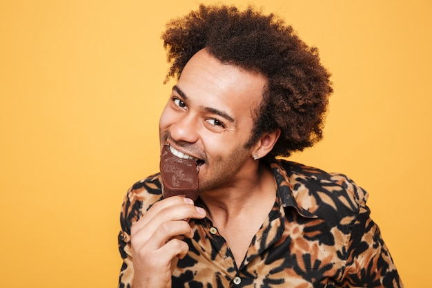 Portrait of a happy young african man eating ice cream