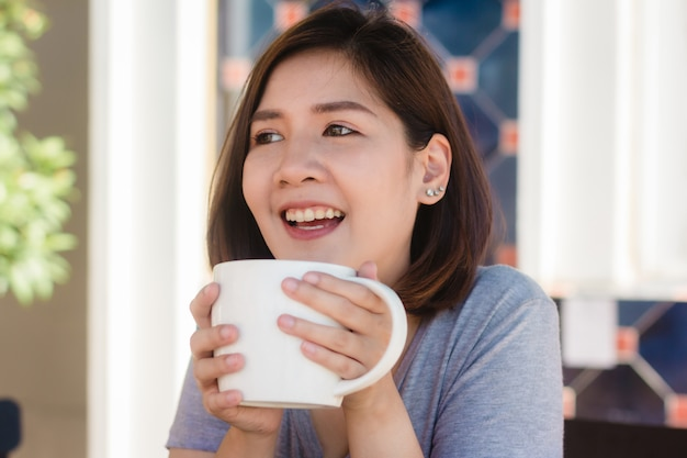 Portrait of happy young asian business woman with mug in hands drinking coffee in the morning