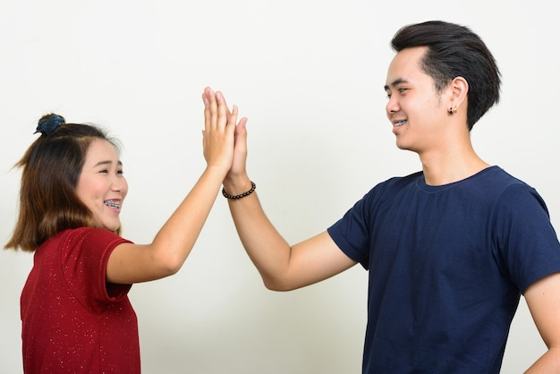 Portrait of happy young asian couple giving high five together