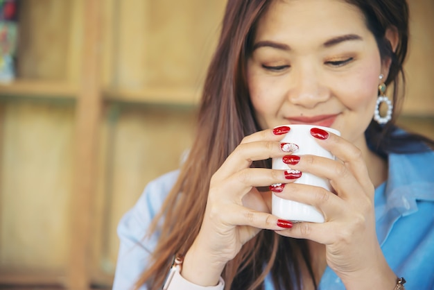 Portrait happy young asian lady in coffee shop