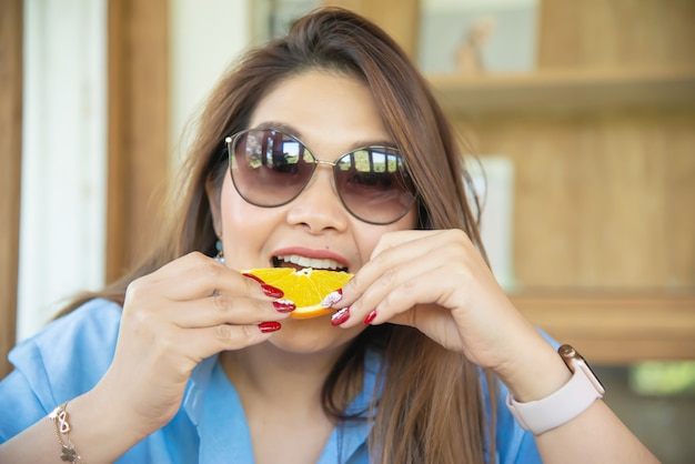 Portrait happy young asian lady eating orange