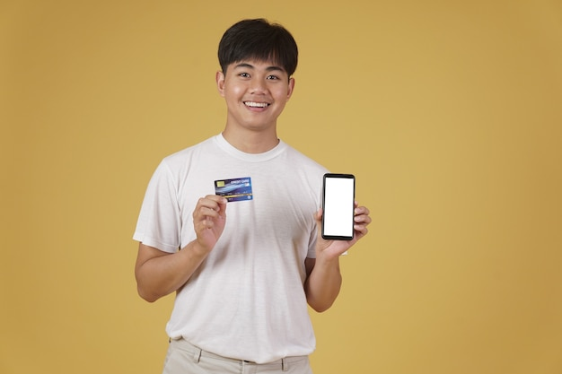 Portrait of happy young asian man dressed casually holding smartphone and credit card for shopping online isolated