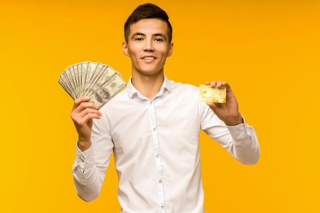 Portrait of happy young asian man holding credit card and money in hand smiling