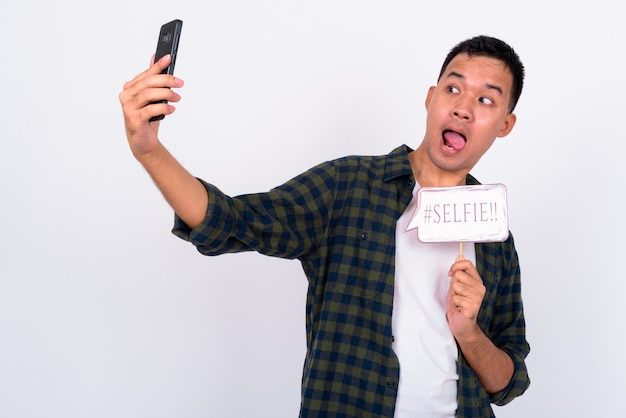Portrait of happy young asian man taking selfie with paper sign
