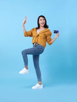 Portrait of a happy young asian woman celebrating with mobile phone and credit card over blue.