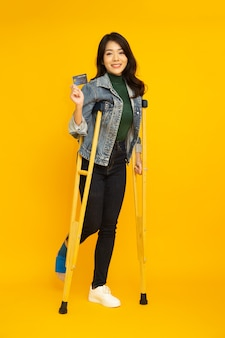 Portrait of a happy young asian woman using a crutch and showing credit card on hand isolated on yellow background, foot injury and personal accident concept