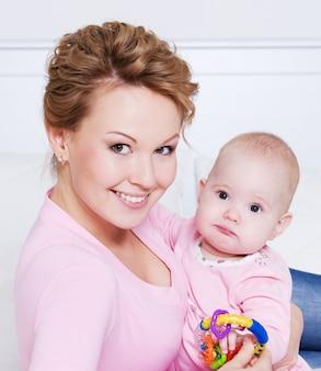 Ritratto di felice giovane madre attactive sdraiata con il suo bambino sul letto di casa