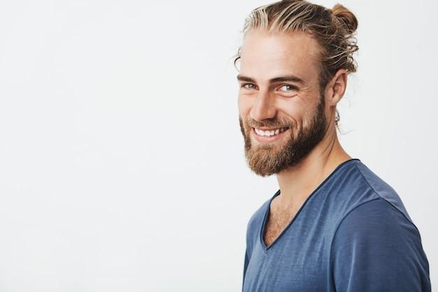 Ritratto di giovane ragazzo barbuto felice con barba e acconciatura alla moda