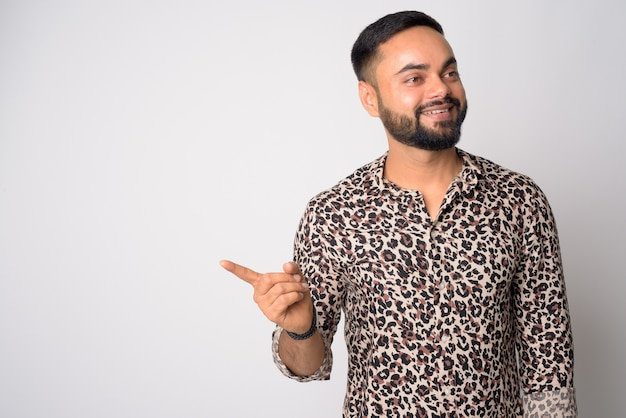Portrait of happy young bearded indian man pointing finger and looking away